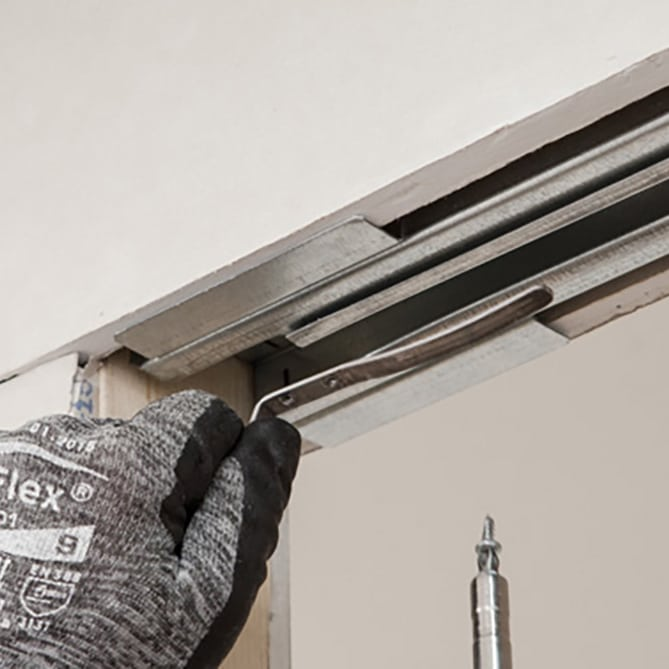 Pictured: This image shows a professional installing a pocket door soft brake system.
